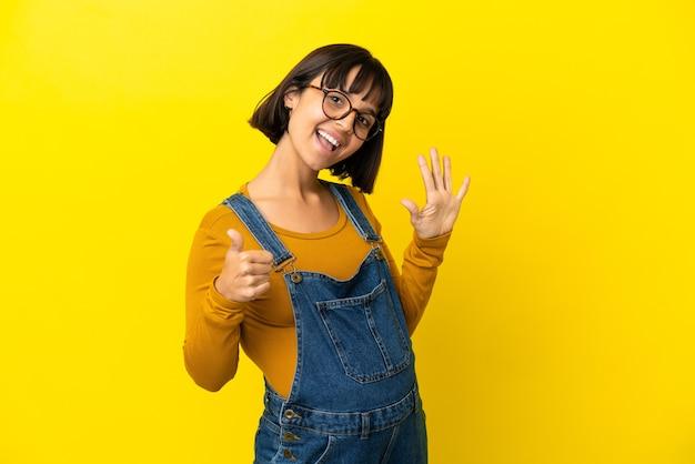 Junge schwangere frau über isoliertem gelbem hintergrund, der sechs mit den fingern zählt