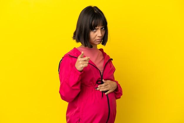 Junge schwangere frau über isoliertem gelbem hintergrund frustriert und zeigt nach vorne