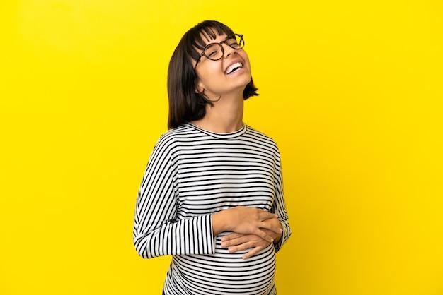 Junge schwangere frau über isoliertem gelbem hintergrund lachen