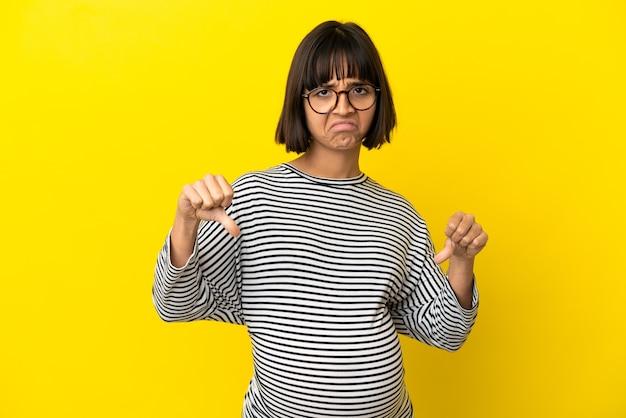 Junge schwangere frau über isoliertem gelbem hintergrund mit daumen nach unten mit zwei händen