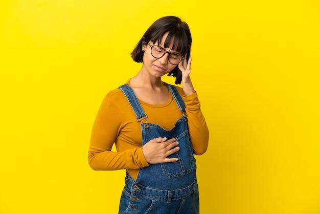Junge schwangere frau über isoliertem gelbem hintergrund mit kopfschmerzen