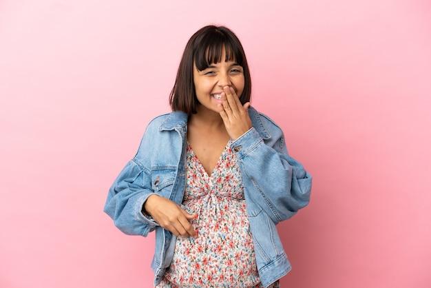 Junge schwangere frau über isoliertem rosa hintergrund glücklich und lächelnd den mund mit der hand bedeckend