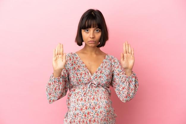 Junge schwangere frau über isoliertem rosa hintergrund macht stop-geste und enttäuscht