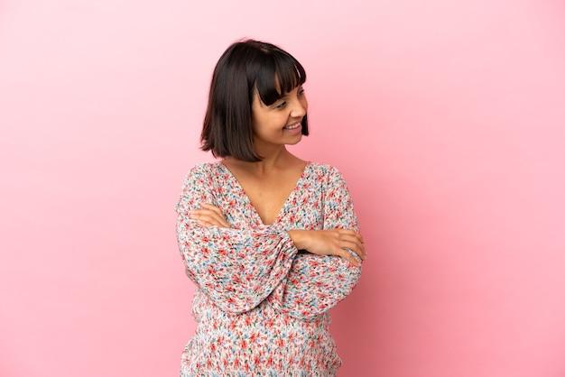 Junge schwangere frau über isoliertem rosa hintergrund mit verschränkten armen und glücklich