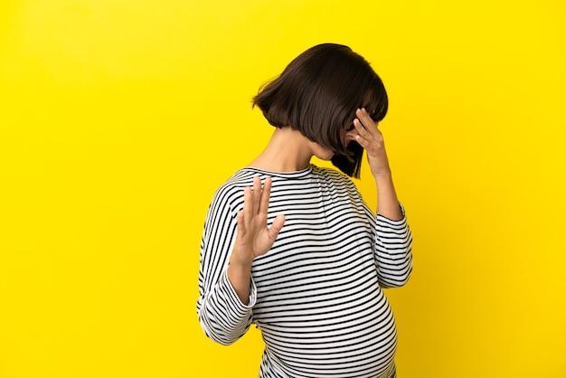 Junge schwangere frau über isolierter gelber wand, die stoppgeste macht und gesicht bedeckt