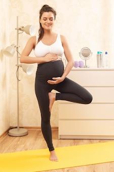 Junge schwangere frau während ihres yoga-trainings zu hause