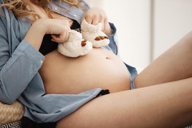 Junge schwangere frauen in schwarzen dessous halten finger in kleinen schuhen auf ihrem dicken bauch und spielen mit kostbarem zukünftigen baby. mutterschaftskonzept