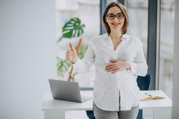 Junge schwangere geschäftsfrau, die am büro steht