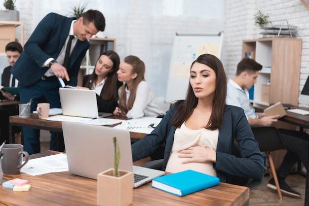 Junge schwangere geschäftsfrau, die im büro arbeitet