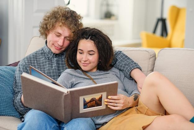 Junge schwangere paare, die ein baby erwarten und auf ihr familienfotobuch schauen