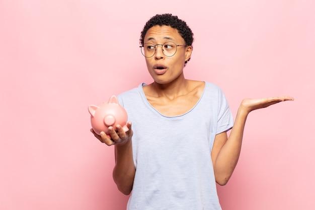 Junge schwarze afro-frau, die überrascht und geschockt aussieht, mit gesenktem kiefer, der einen gegenstand mit einer offenen hand auf der seite hält