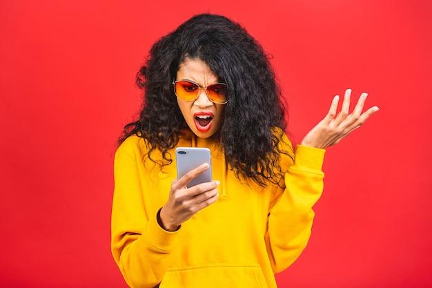 Junge schwarze afroamerikanerfrau mit sonnenbrille lokalisiert über rotem hintergrund