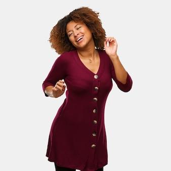 Junge schwarze afrofrau, die spaß tanzt und hat