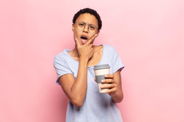 Junge schwarze afrofrau mit weit geöffnetem mund und augen und hand am kinn, die sich unangenehm schockiert fühlt, was sagt oder wow