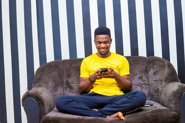 Junge schwarze college african millennial hipster mit handy aufgeregt im chat mit freunden networking