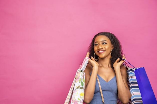 Junge schwarze dame, die einkaufstaschen hält, die aufgeregt fühlen