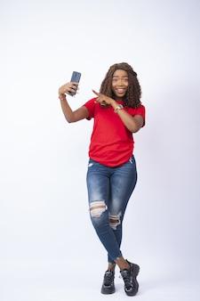 Junge schwarze dame, die ihr telefon hält und mit aufregung im gesicht darauf zeigt