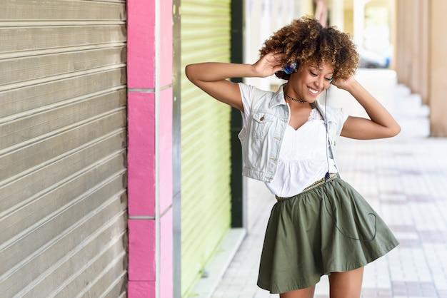 Junge schwarze frau, afrofrisur, in der städtischen straße mit kopfhörern