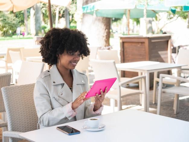 Junge schwarze frau auf einem kaffeegeschäft und das überprüfen des internets auf einer rosa tablette