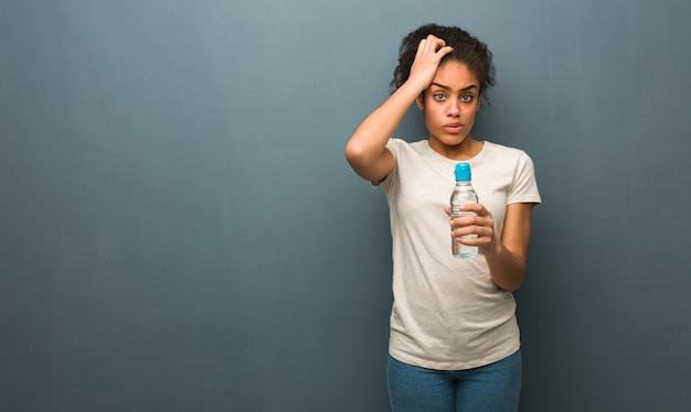 Junge schwarze frau besorgt und überwältigt. sie hält eine wasserflasche.