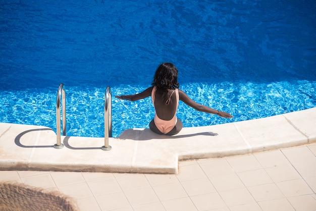Junge schwarze frau, die am rand eines pools mit dem kühlen blauen wasser ein sonnenbad nimmt abkühlt.