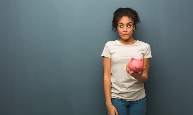 Junge schwarze frau, die an eine idee denkt. sie hält ein sparschwein.