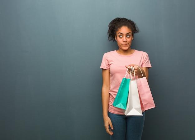 Junge schwarze frau, die an eine idee denkt. sie hält eine einkaufstüte.
