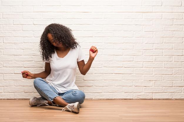 Junge schwarze frau, die auf bretterboden sitzt musik hören, spaß tanzen und haben