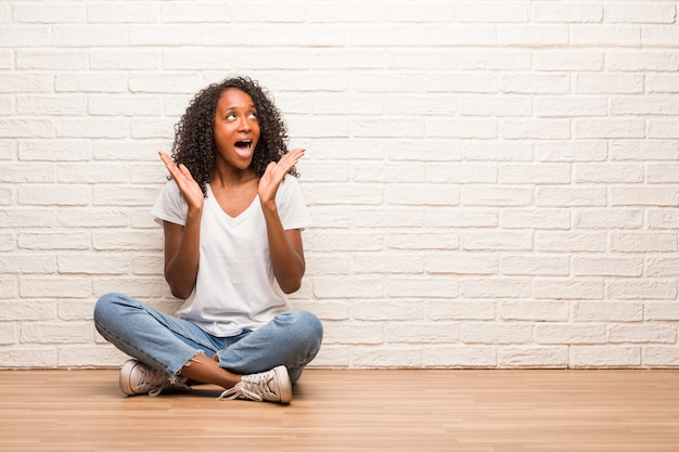 Junge schwarze frau, die auf dem bretterboden überrascht und entsetzt sitzt und mit großen augen schaut, aufgeregt durch ein angebot oder durch einen neuen job, gewinnkonzept