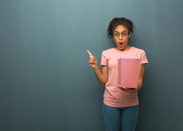 Junge schwarze frau, die auf die seite zeigt. sie hält einen popcorn-eimer in der hand.