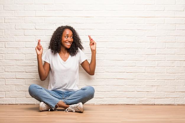 Junge schwarze frau, die auf einem bretterboden sitzt, der seine finger kreuzt