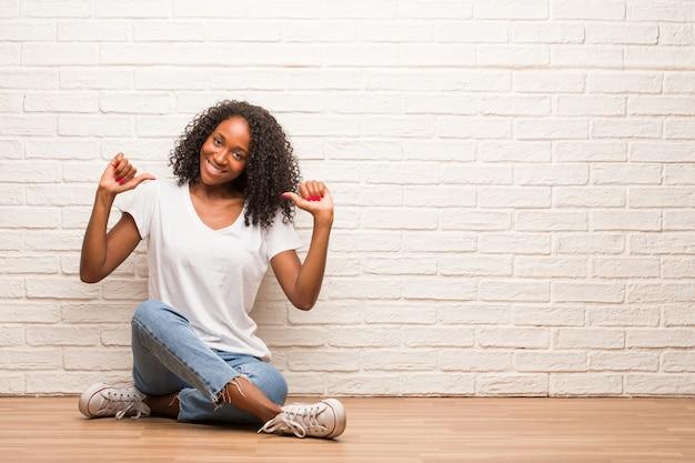 Junge schwarze frau, die auf einem bretterboden stolz und überzeugt sitzt und finger, beispiel zum folgen, konzept der zufriedenheit, arroganz und gesundheit zeigt
