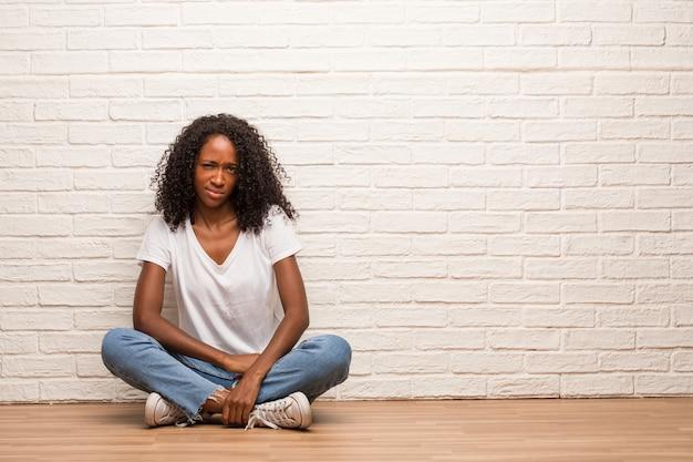 Junge schwarze frau, die auf einem bretterboden zweifelnd und verwirrt sitzt, an eine idee denkt oder an etwas gesorgt ist