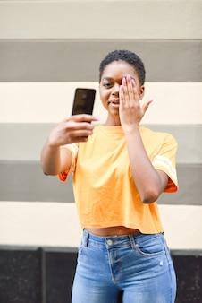 Junge schwarze frau, die draußen selfie fotos mit lustigem ausdruck macht