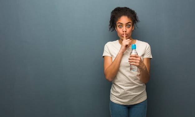 Junge schwarze frau, die ein geheimnis hält oder um ruhe bittet. sie hält eine wasserflasche.