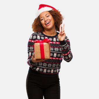 Junge schwarze frau, die ein geschenk am weihnachtstag eine geste des sieges tut