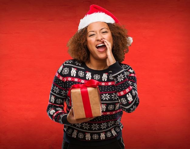 Junge schwarze frau, die ein geschenk am weihnachtstag etwas glücklich schreiend zur front hält