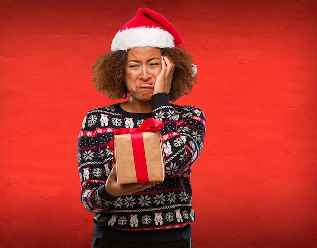 Junge schwarze frau, die ein geschenk am weihnachtstag hoffnungslos und traurig hält