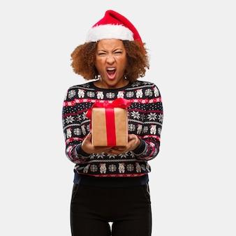 Junge schwarze frau, die ein geschenk am weihnachtstag sehr verärgert und aggressiv schreiend anhält
