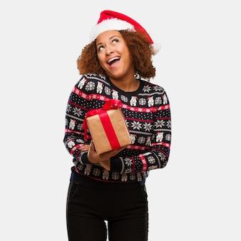 Junge schwarze frau, die ein geschenk am weihnachtstag träumt vom erreichen von zielen und von zwecken hält