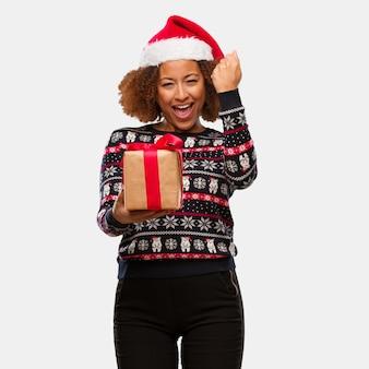 Junge schwarze frau, die ein geschenk am weihnachtstag überrascht und entsetzt hält