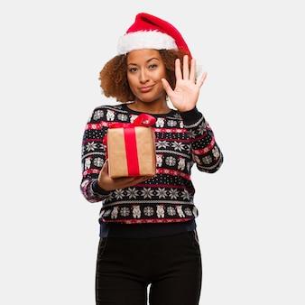 Junge schwarze frau, die ein geschenk am weihnachtstag zeigt nr. fünf hält