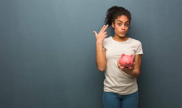 Junge schwarze frau, die eine selbstmordgeste tut. sie hält ein sparschwein.