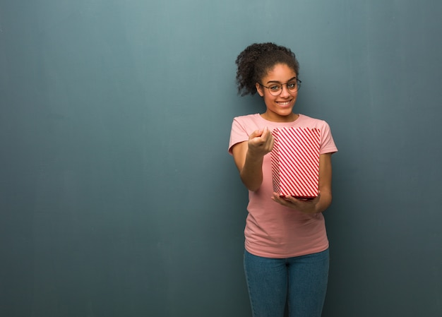 Junge schwarze frau, die einlädt zu kommen. sie hält einen popcorn-eimer in der hand.