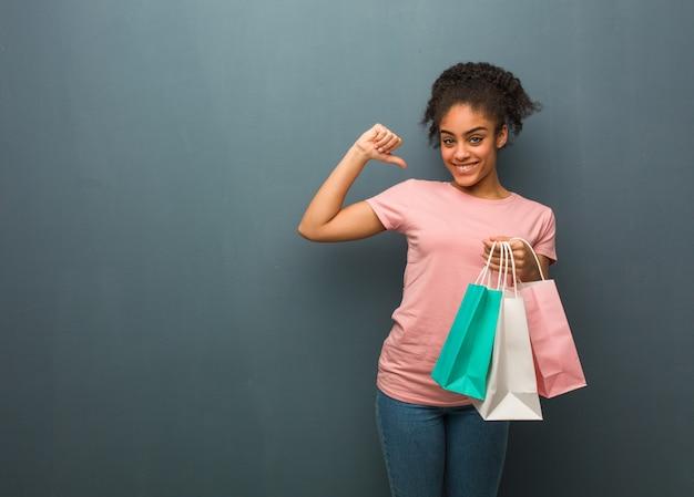 Junge schwarze frau, die finger zeigt, um zu folgen beispiel. sie hält eine einkaufstüte.