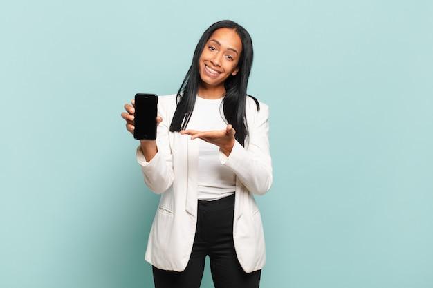 Junge schwarze frau, die fröhlich lächelt, sich glücklich fühlt und ein konzept im kopierraum mit der handfläche zeigt. smartphone-konzept