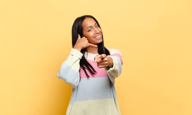 Junge schwarze frau, die fröhlich lächelt und auf die kamera zeigt, während sie einen anruf tätigen, den sie später gestikulieren, telefonieren