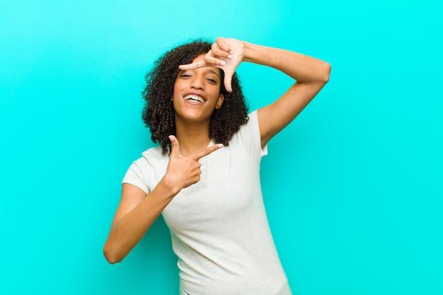 Junge schwarze frau, die glücklich, freundlich und positiv fühlt, lächelt und ein porträt oder fotorahmen mit händen gegen blaue wand macht