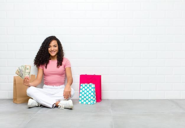 Junge schwarze frau, die glücklich mit einer hand auf hüfte und selbstbewusster, positiver, stolzer und freundlicher haltung lächelt, die auf dem boden sitzt