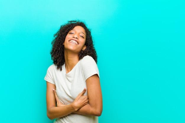 Junge schwarze frau, die glücklich mit verschränkten armen lacht, mit einer entspannten, positiven und zufriedenen haltung auf blauer wand